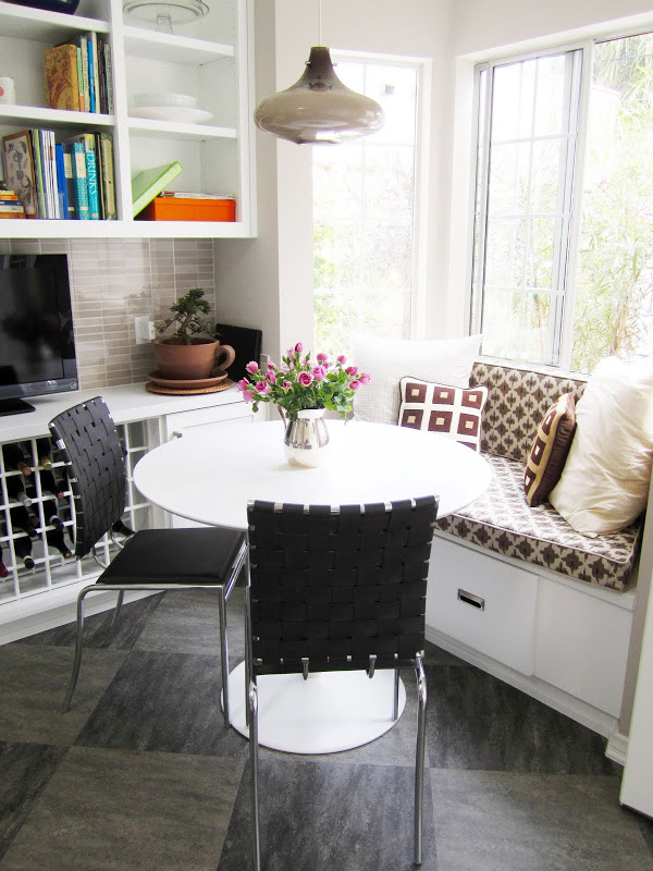 Breakfast nook with banquette seating, a pendant light and two black chairs with woven seats and backs