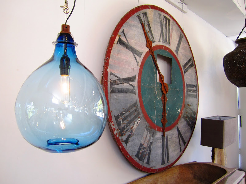 Blue glass jug pendant light and a large clock at Cisco Home in Brentwood