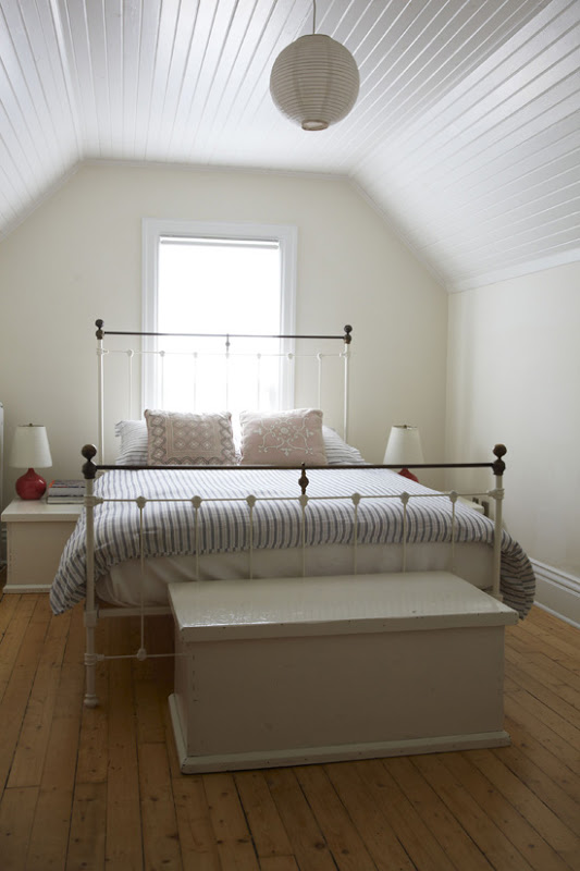 White bedroom with white beadboard ceiling, wide plank wood floor, white iron bed frame and a white lantern