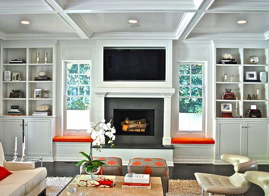 Den with coffered ceiling, built in bookshelves with windows seats with orange cushions, dark wood floor, a shag rug, two grey square stools with orange polka dots and two leather chairs with a white sofa