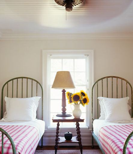 Bedroom with two twin wrought iron beds with arched headboards, red gingham bedding, beadboard ceiling and a wood nightstand between the beds