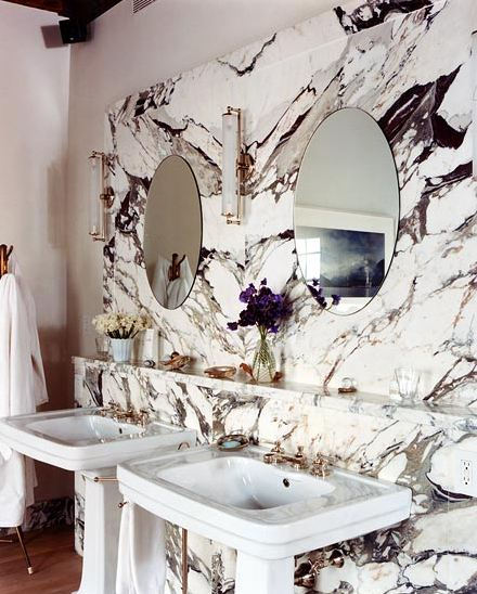 Bathroom with veiny marble for the wall of the sink, pedestal sinks and round mirrors