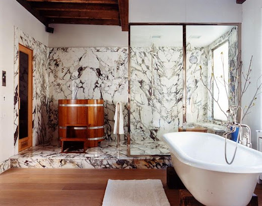 Bathroom with colorful marble in the shower area which is also adorned with a standing wood soaking tub, wood floor, and a stand alone tub