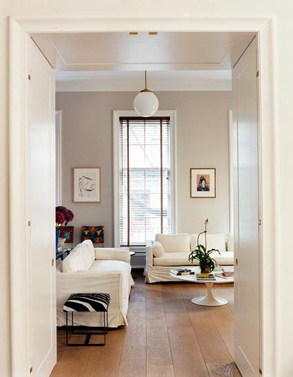 Den with white slipcovered sofas, a Saarinen tulip coffee table, zebra upholstered stool, wide planked wood floors, white globe light and a tall window