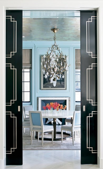 Dining room by Peter Pennoyer with light blue walls with decorative moulding, a fireplace, branch inspired crystal chandelier, round table surrounded by white upholstered chairs and black pocket doors