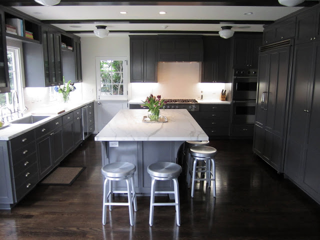 Kitchen with dark grey cabinets and drawers, marble counter tops, wood floor, and metal barstools around a large island with a marble top