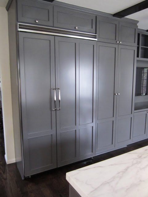 Kitchen with a double refrigerator concealed behind custom paneling