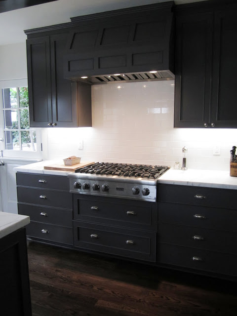 Kitchen with a Viking gas range with a paneled hood painted grey to match the cabinets and drawers