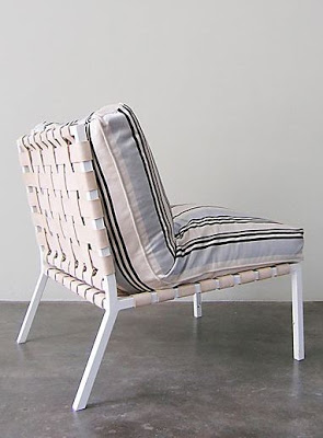 Chair with white leather straps make up seat and back, painted iron base
