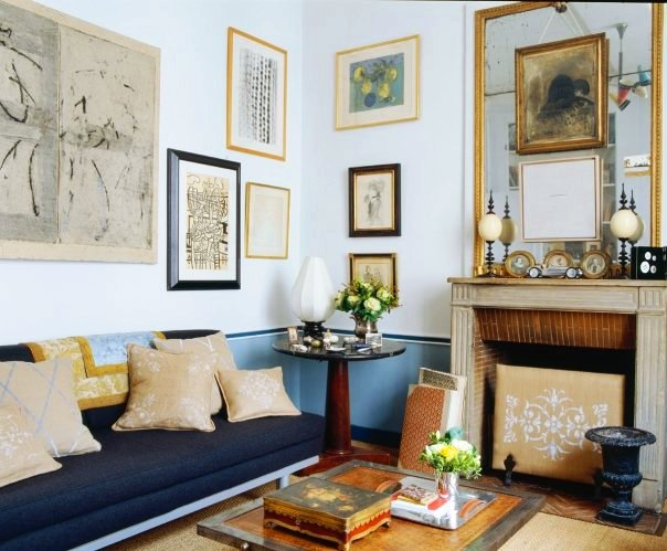 Living room with a blue sofa with light blue exposed legs, tan accent pillows, a fireplace with a large gold framed mirror, light blue walls covered in art