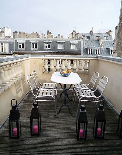 Roof top patio in Paris with metal seats, a white oval table with black metal legs and black lanterns with pink candles