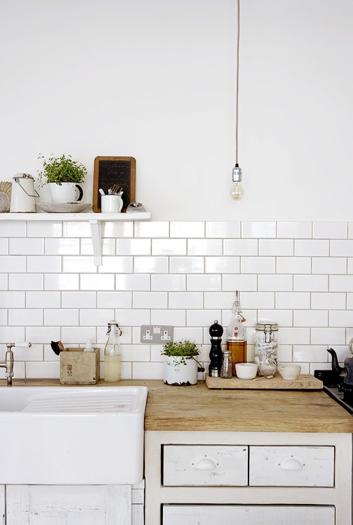 Close Up Of The Exposed Bulb Lighting White Subway Tile Backsplash With Dark Grout Lines