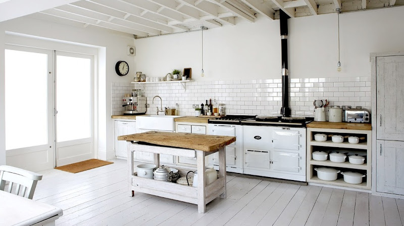 White rustic eat in kitchen with white washed floors and cabinetry, exposed bulb lighting, white subway tile backsplash with dark grout lines, and reclaimed butcher block counter tops.