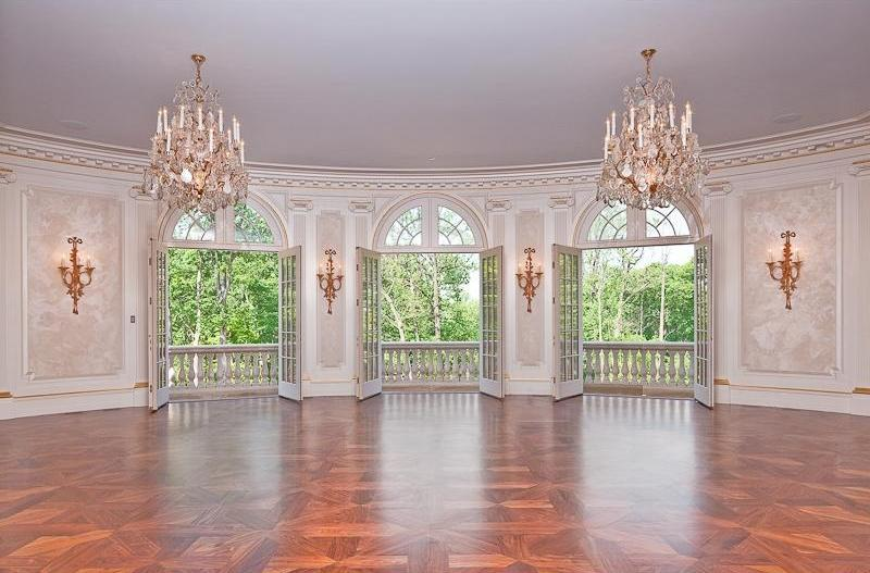 Living room with two crystal chandeliers, wood floor, french doors opening to a balcony, paneled walls, wall mounted candle holders and moulded ceiling