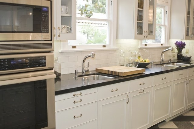 Tom Newman's kitchen with plaid tile floor, black counter top, white cabinets and stainless appliances