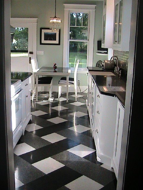 Kitchen after it's Tom Newman inspired makeover with a plaid tile floor, black counter top, white cabinets, mint walls and stainless appliances
