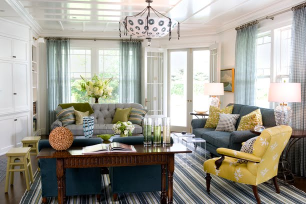 Living room with a gingham sofa, striped rug, blue armchairs, a yellow and white armchair, a blue sofa, sheer gingham curtains, a white and blue light and a coffered ceiling