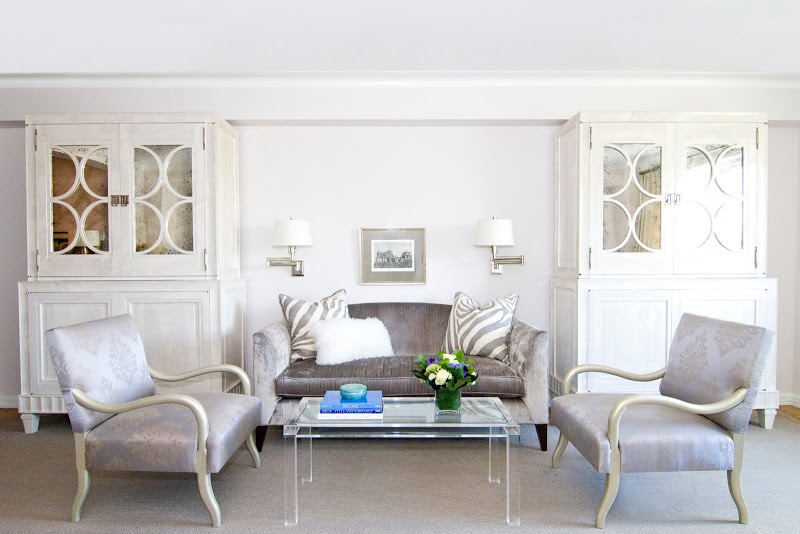 Elegant, kid friendly living room in NYC with lavender armchair and sofa, a lucite coffee table, light grey carpeting, two wall mounted lights and two large white cabinets