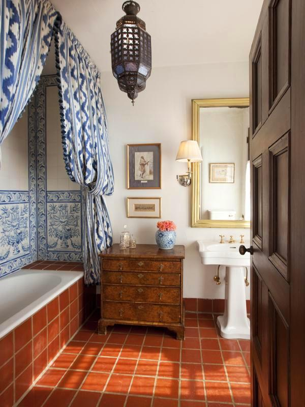 Bathroom in a Montecito mansion with blue and white ikat curtains instead of a glass door to the tub, a built in tub with, blue and white Portuguese tile line the back wall, a pedestal sink, a wood chest of drawers and a Moroccan lantern light