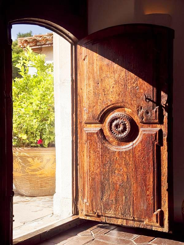 Carved, arched front door to a Montecito mansion with terra cotta tile floor