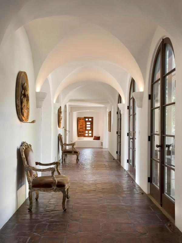 Hallway in a Montecito mansion with vaulted ceiling, arched doors and saltillo tile floor