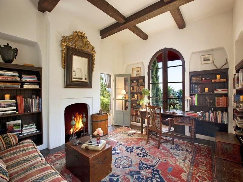 Library in a Montecito mansion with a fireplace and a mirror in a traditional frame on the mantel, built in bookshelves, arched windows, a wood desk and chair, a striped sofa and a large Turkish rug