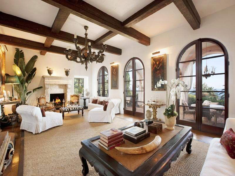 Living room in a Montecito mansion with exposed beams, wood floor, a tan rug, chandelier, white armchairs and sofa and high arched doors leading to a balcony