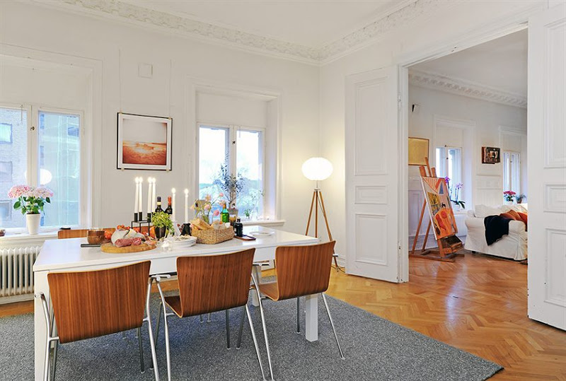 Kitchen in a Swedish apartment with herringbone wood floor, carved crown molding, the decorative ceiling medallions, tall paneled doors, grey rug and a white table surrounded by wood chairs with metal arms and legs