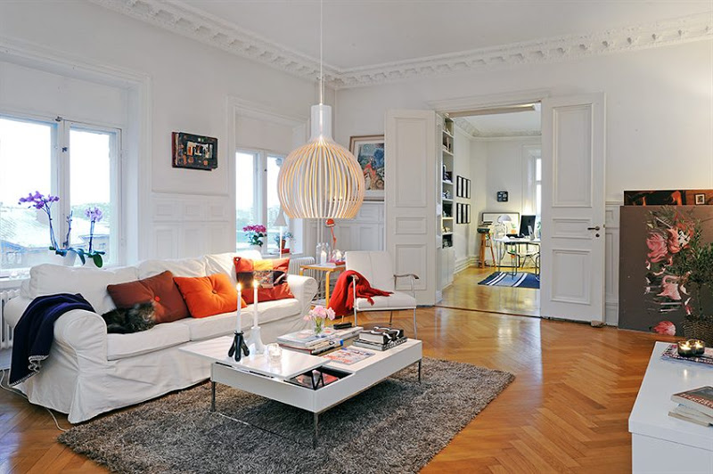 Living room with herringbone wood floor, carved crown molding, the decorative ceiling medallions, tall paneled doors, a white sofa with orange accent pillows, a brown rug, cage pendant light, and a white armchair