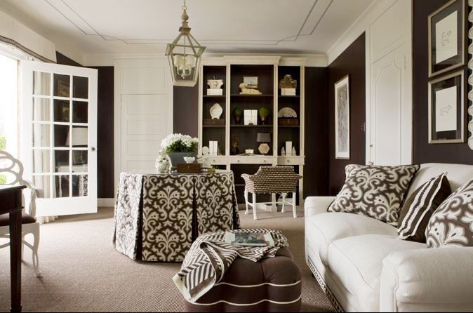 Sitting room with brown walls, a white sofa, tufted brown ottoman with white piping, a lantern, built in bookshelf and a round table with a brown and white table cloth