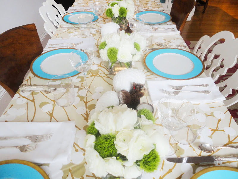 Holiday table setting with flower arrangements made of white Peonies, Ranunculus and green PomPoms, blossom tablecloth by Marimekko from Crate and Barrel, turquoise blue rimmed china, white ceramic pine cones and squirrels