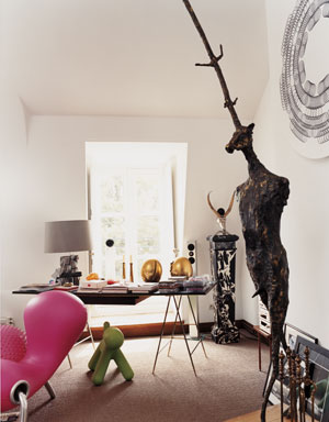 Yves Gastou's home office with a black desk on thin metal legs, a large window and lots of modern art sculptures