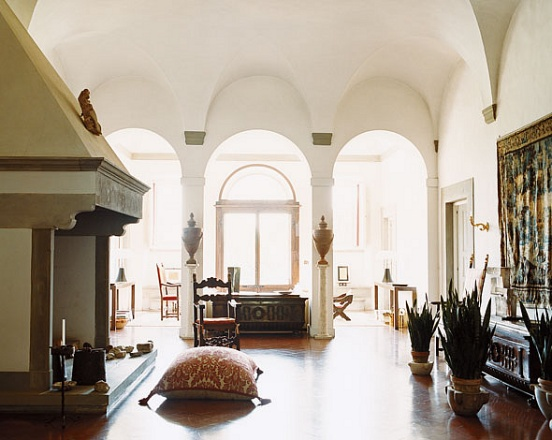 Living from in an Italian estate with wood floor, grand fireplace, arched entryways, plants and dark wood tables and chair