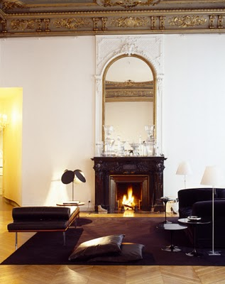 Living room with herringbone wood floor, carved dark wood fireplace, a tall arched mirror with decorative frame, molded ceiling, a large dark purple rug, a black chaise lounge and a matching sofa with two tulip side tables