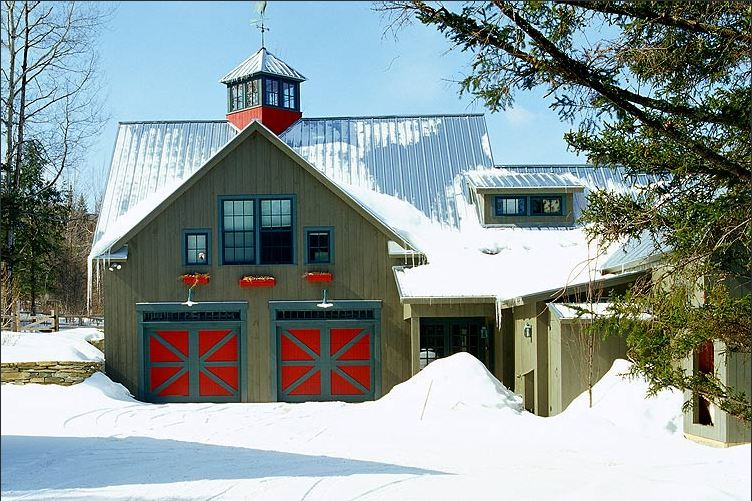 Exterior of a green barn with red and blue doors covered in snow