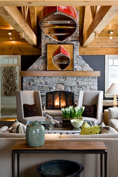 Living room in a cabin with knotty wood floor, grey sofa and armchairs with high backs, a flagstone fireplace, exposed beams and a red, upside down canoe hanging from the ceiling