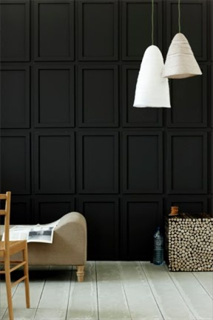 Living room with matte black paneled walls, two white pendant lights, grey wood floor, a taupe chaise lounge and a simple wooden chair