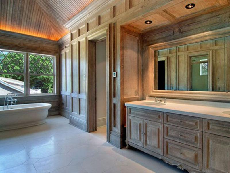 Master bathroom with tile floor, wood paneled walls and cabinets, wood ceiling and a stand alone tub