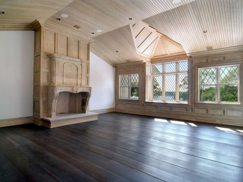 master bedroom with light wood paneling and ceiling wood floor and a fireplace - Wood Paneling With Wood Floor
