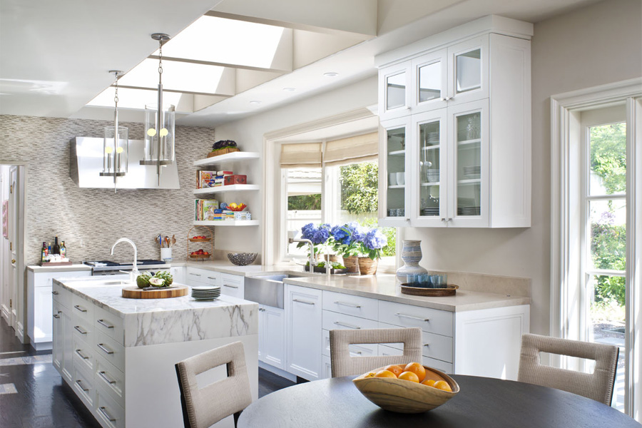 Bright kitchen with skylight, pendant lights, white cabinets and drawers  with long silver pulls