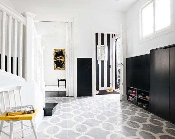 Foyer with Moroccan cement tile entryway floor in charcoal grey, black cabinets, white walls and a white staircase