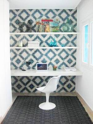 Blue and white diamond cement tiles behind a white desk with floating shelves. In front of the desk is a white Tulip Chair on a dark rug with a diamond pattern
