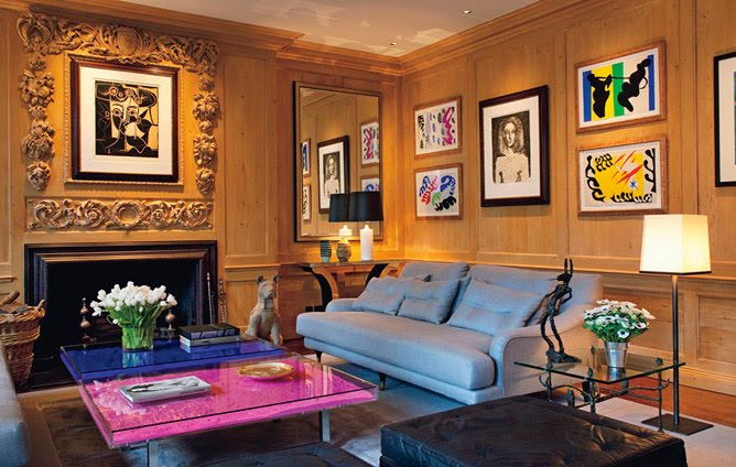 Living room with Yves Klein's Table Bleue and Table Rose, wood paneled walls covered in frames pieces of art, a fireplace with an intricately carved mantel, a leather sofa, a black tufted leather ottoman and a glass side table
