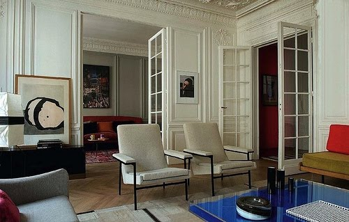 Living room with Yves Klein's Table Bleue, white walls with decorative moulding, French doors, herringbone wood floors, two armchairs and dueling sofas