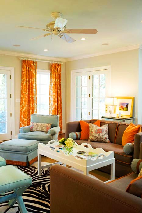 TV room with brown sofas, zebra print rug, orange and white brocade curtains, French doors, blue armchair with matching ottoman and two blue x-benches
