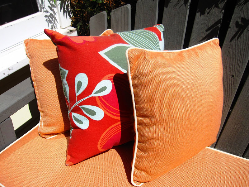 Close up of the orange floral accent pillows on a grey Adirondack love seat on the front porch of a cottage in Venice Beach, CA