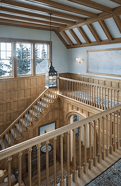 Exposed beam angled ceiling and more carved woodwork on the railing of the second floor landing in a home by Peter Pennoyer