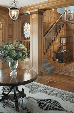 Entry hall in a home by Peter Pennoyer with wood carvings and paneling