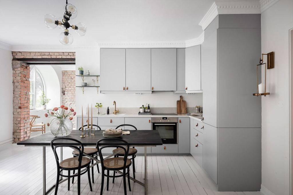 Grey kitchen with an exposed brick wall