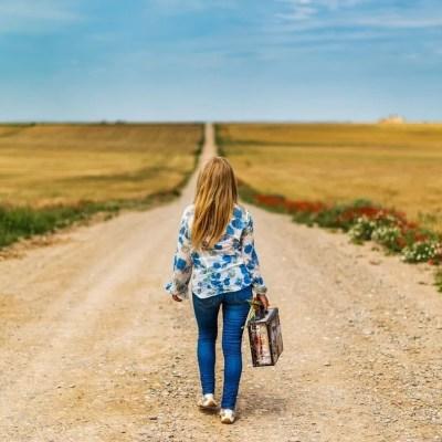 Girl walking along dusty road